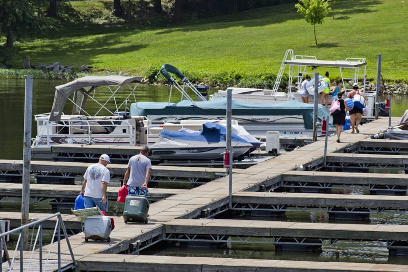 Guests bringing fishing equipment down the dock.