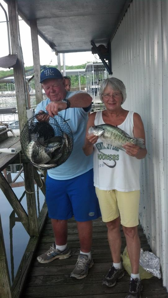 Older couple holding a basket of fish.