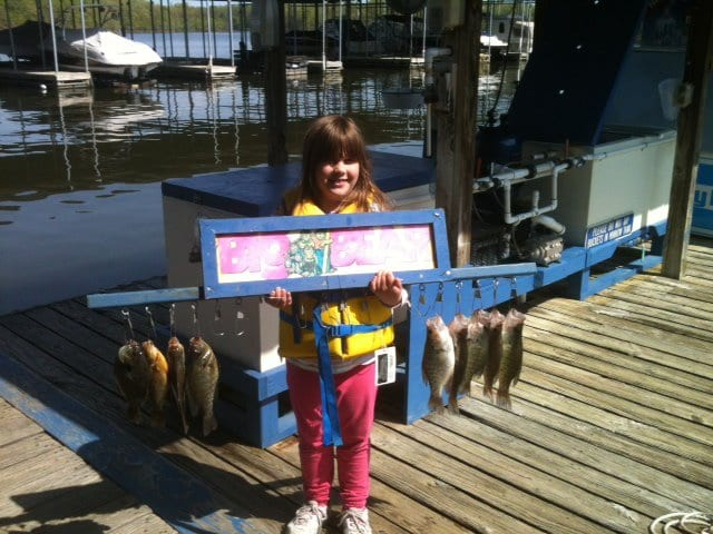 Young girl holding several fish on a rack.